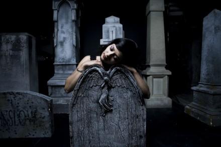 immagine di una giovane e bella donna gotica appoggiata sulla lapide per poesia di de oculta tecnologia